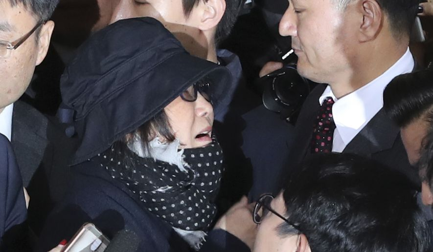 Choi Soon-sil, center left, a cult leader's daughter with a decades-long connection to President Park Geun-hye, is surrounded by prosecutor's officers and media upon her arrival at the Seoul Central District Prosecutors' Office in Seoul, South Korea, Monday, Oct. 31, 2016. South Korea is hoping for answers Monday about its biggest scandal in years. (AP Photo/Lee Jin-man)