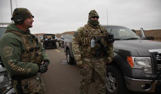 Two members of the Stutsman County SWAT team talk while deployed to watch protesters demonstrating against the Dakota Access Pipeline encroaching the water source near the Stand Rock Sioux Reservation, as they stand next to a police barricade on Highway 1806 in Cannon Ball, N.D., Sunday, Oct. 30, 2016. (AP Photo/John L. Mone)
