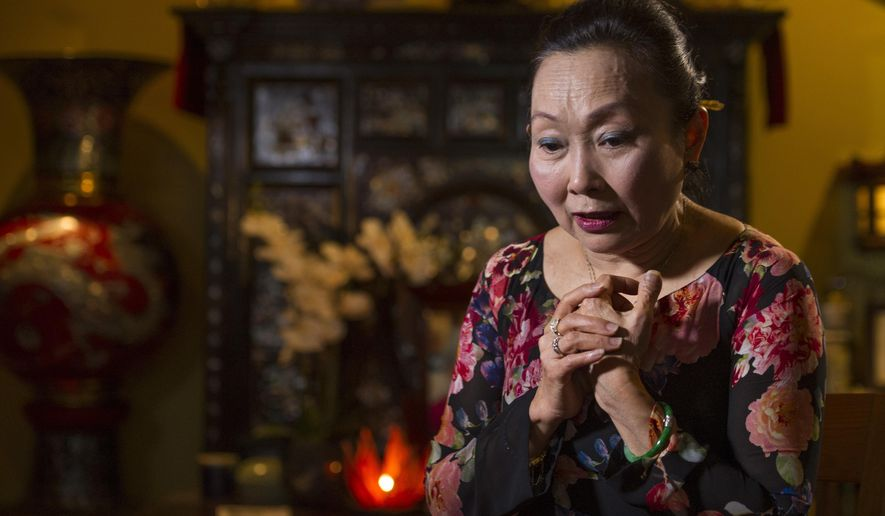 In this photo taken Oct. 20, 2016, Kim Ha-Ly, 67, with her Buddhist shrine behind her, talks about her political beliefs in her Woodbridge, Va., home. Vietnamese and other Asian-Americans have shifted from being majority Republican supporters to overwhelmingly Democrat. Donald Trump's polarizing rhetoric on issues like immigration could accelerate the trend. That shift could have an effect on the presidential race.  (AP Photo/Cliff Owen)