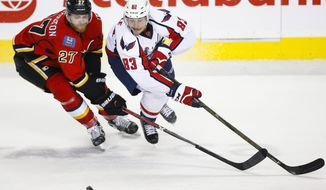 Washington Capitals' Jay Beagle, right, and Calgary Flames' Dougie Hamilton chase a loose puck during second period NHL hockey action in Calgary, Alberta, Sunday, Oct. 30, 2016. (Jeff McIntosh/The Canadian Press via AP)