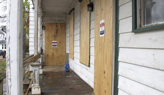 U.S. Marshal no trespassing signs are attached to pieces of plywood covering doors and windows of a house Monday, Oct. 31, 2016 in Rutland, Vt. Local, state and federal officials announced Monday that three structures once considered drug houses on Park Avenue, in Rutland, that were seized by the U.S. Government are going to be turned into owner-occupied homes as part of a broader effort to fight drugs. The properties were turned over to the city, which in turn transferred ownership to the group NeighborWorks of Western Vermont, which will rehabilitate them and then sell them. (AP Photo/Wilson Ring)