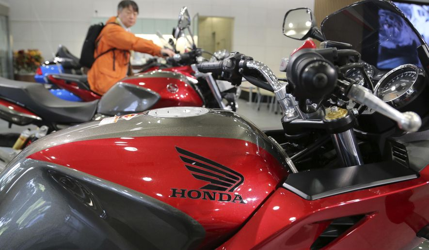 A man checks a Honda motorcycle displayed at the Honda Motor Co. headquarters showroom in Tokyo, Monday, Oct. 31, 2016. Honda says its net profit in the last quarter was 188 billion yen ($1.7 billion), up 39 percent from a year earlier. (AP Photo/Koji Sasahara)