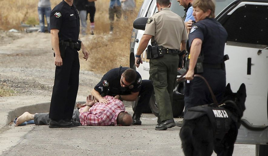 A Grand Junction, Colo., Police Department officer kneels over a handcuffed James Main Jr., while another officer stands by following Main's capture Sunday, Oct. 30, 2016, in Grand Junction, Colo. Authorities in Grand Junction said Sunday they have arrested Main, a homicide suspect wanted in Utah. (Gretel Daugherty/The Grand Junction Daily Sentinel via AP)