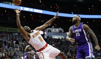 Atlanta Hawks' Dwight Howard, center, puts up a shot against the defense of Sacramento Kings' Ty Lawson, left, and DeMarcus Cousins in the second quarter of an NBA basketball game in Atlanta, Monday, Oct. 31, 2016. (AP Photo/David Goldman)