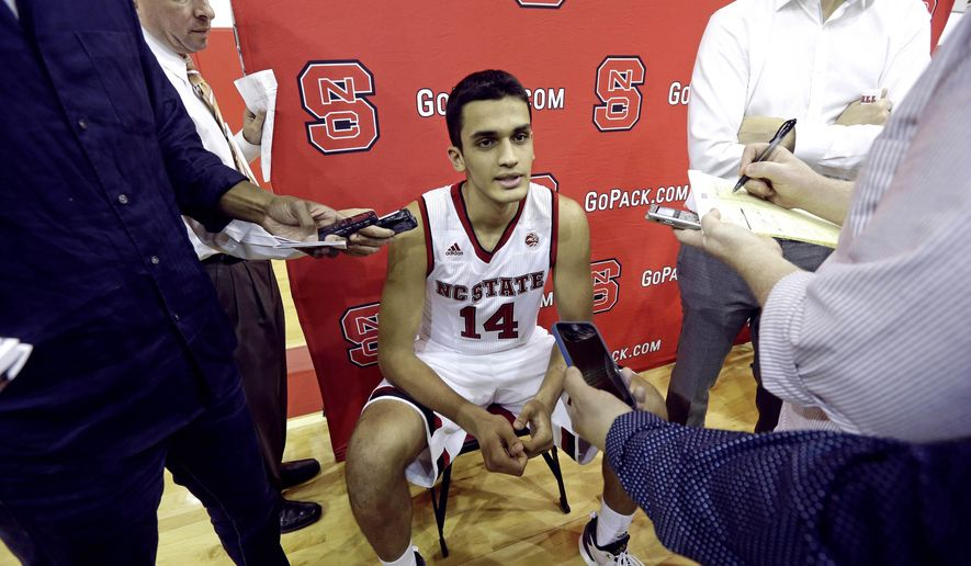 FILE - In this Sept. 29, 2016, file photo, North Carolina State's Omer Yurtseven, of Turkey, takes questions during the NCAA college basketball team's media day in Raleigh, N.C.  The NCAA has ruled that NC State freshman center Yurtseven must sit the first nine regular-season games and pay $1,000 to a charity of his choice after a review of his time playing overseas. (AP Photo/Gerry Broome, File)