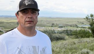 FILE - In this Aug. 26, 2016 file photo, Standing Rock Sioux Chairman Dave Archambault II poses for a photo near Cannon Ball., N.D., on the Standing Rock Sioux Reservation overlooking an encampment where Native Americans are gathered to join his tribe's growing protest against the Dakota Access oil pipeline. The reservation on the North Dakota-South Dakota border sits close to the pipeline's path. (AP Photo/James MacPherson, File)