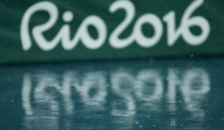 FILE - In this  Aug. 15, 2016 file photo, the Olympic logo is reflected on the wet floor as the athletics competitions of the Summer Olympics are suspended due to the pouring rain in Rio de Janeiro, Brazil. Workers employed at the Rio Olympics are ready to sue the organizing committee for late payments more than 2 1/2 months after the problem-filled games ended. (AP Photo/Matt Slocum, File)