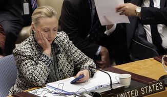 Then-Secretary of State Hillary Rodham Clinton checks her mobile phone after her address to the Security Council at United Nations headquarters. (AP Photo/Richard Drew, File)