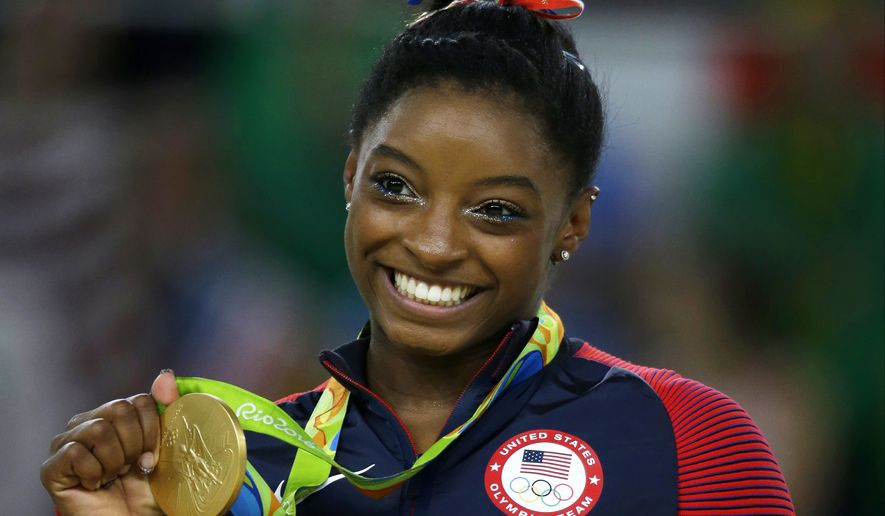 FILE - In this Aug. 16, 2016 file photo, United States gymnast Simone Biles displays her gold medal for floor during the artistic gymnastics women's apparatus final at the 2016 Summer Olympics in Rio de Janeiro, Brazil. (AP Photo/Rebecca Blackwell, File) **FILE**