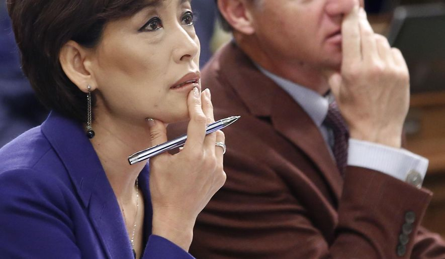 FILE - In this June 19, 2015, file photo, Republican Assembly members Young Kim, of Fullerton, and Brian Jones, of Santee, watch as the votes are posted for the revised budget plan up for consideration at the Capitol in Sacramento, Calif. Kim's campaign says someone stole 30 tablets and a laptop computer from her Orange County campaign office. (AP Photo/Rich Pedroncelli, File)