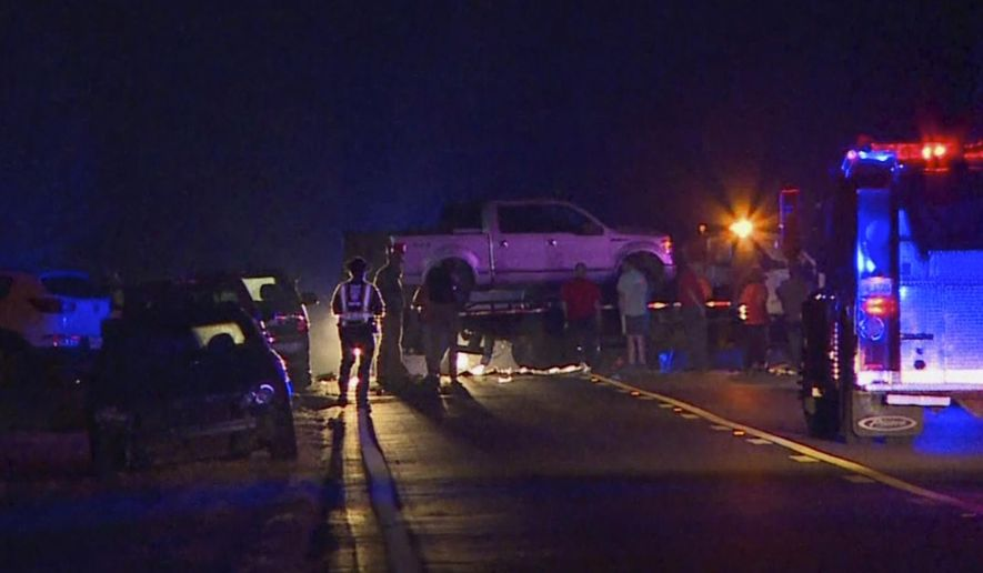 CORRECTS SOURCE NAME TO WTOK-TV FROM WTO - In this image made from video, people gather around a pickup truck on a flatbed truck at the scene of an accident on U.S. Highway 80 in Chunky, Miss., late Monday, Oct. 31, 2016. A vehicle struck the flat-bed trailer carrying adults and children who were dressed up for Halloween, killing multiple people and injuring several others, authorities said. (WTOK-TV via AP)