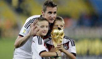 FILE - The July 13, 2014 file photo shows Germany's Miroslav Klose posing with the World Cup trophy and his sons following their 1-0 victory over Argentina after the World Cup final soccer match between Germany and Argentina at the Maracana Stadium in Rio de Janeiro, Brazil.  The German soccer federation says Tuesday Nov. 1, 2016 striker Miroslav Klose, the top scorer in World Cup history, is ending his playing career and will train as a coach.  (AP Photo/Natacha Pisarenko,file)