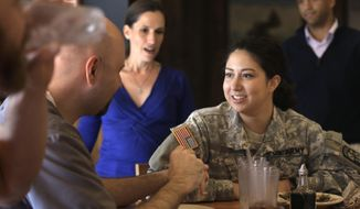 In this Thursday, Oct. 13, 2016 photo Brown University student and U.S. Army ROTC cadet Maddy Gonzalez, of Tacoma, Wash., in uniform at center right, speaks with U.S. Navy veteran and Brown student Chris Baker, of Warwick, R.I., second from left, during a luncheon at a pizza restaurant near Brown's campus, in Providence, R.I. The luncheon was hosted by the university to make student veterans more welcome on campus. Karen McNeil, Brown University program director in the office of student veterans and commissioning programs, looks on behind left. (AP Photo/Steven Senne)