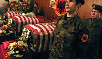 FILE - In this March 3, 2002 file photo, a KLA-Kosovo Liberation Army honor guard stands besides the coffins of, from right, Ylli Bytyqi, Agron Bytyqi and Mehmet Bytyqi, during a wake held in the Bronx borough of New York City. A brother of the slain Bytyqi brothers accused Serbia's leaders on Tuesday, Nov. 1, 2016, of protecting the killers and refusing to bring them to justice despite repeated pledges to U.S. officials to do so. (AP Photo/Shawn Baldwin, File)