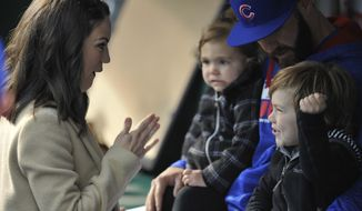 FILE - In this April 26, 2016, file photo, Chicago Cubs pitcher Jake Arrieta, wife Brittany, daughter, Palmer, and son, Cooper, wait in a dugout before a ceremony honoring Arrieta before the Cubs' baseball game against the Milwaukee Brewers in Chicago. Brittany Arrieta shared photos on Instagram Oct. 31, 2016, of the family celebrating Halloween in a hotel room ahead of Game 6 of the World Series in Cleveland on Nov. 1, 2016. (AP Photo/Paul Beaty, File)