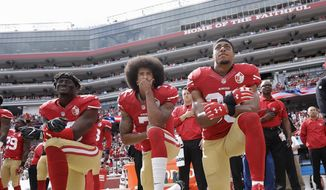 In this Oct. 2, 2016, file photo, from left, San Francisco 49ers outside linebacker Eli Harold, quarterback Colin Kaepernick and safety Eric Reid kneel during the national anthem before an NFL football game against the Dallas Cowboys in Santa Clara, Calif. (AP Photo/Marcio Jose Sanchez, File)