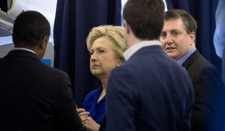 Democratic presidential candidate Hillary Clinton, second from left, speaks with traveling political adviser Darren Peters, left, traveling press pecretary Nick Merrill, and outside adviser Philippe Reines, right, on board her campaign plane at Fort Lauderdale-Hollywood International Airport in Fort Lauderdale, Fla., Wednesday, Nov. 2, 2016, before traveling to Las Vegas. (AP Photo/Andrew Harnik) ** FILE **