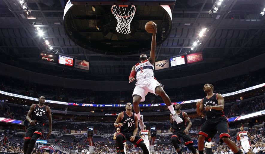 Washington Wizards guard John Wall (2) shoots in front of Toronto Raptors forward Pascal Siakam (43), guard DeMar DeRozan (10) and guard Kyle Lowry (7) during the first half of an NBA basketball game Wednesday, Nov. 2, 2016, in Washington. (AP Photo/Alex Brandon)
