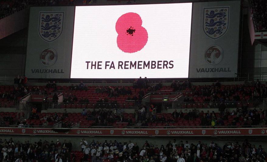 In this Saturday, Nov. 12, 2011, file photo, a poppy is displayed on a big screen for Armistice Day before the international friendly soccer match between England and Spain at Wembley Stadium in London. (AP Photo/Kirsty Wigglesworth, file) **FILE**