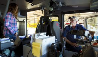 ADVANCE FOR THE WEEKEND OF NOV. 5 & 6 AND THEREAFTER - Robert Hauber, right, shows his granddaughter Jasmyn Kalpin, 11, around the cab of a Campbell County Fire Department engine during Hauber's retirement party last week at Station 1, Sept. 30, 2016, in Gillette, Wy. Hauber, his brother Richard and father Walt all together have 134 years of experience fighting fires in Campbell County. /Gillette News Record via AP)