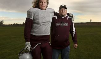 Logan Harris poses with his dad James at Torrington High School's practice field on Oct. 11, 2016, in Torrington, Wyo. Logan, a linebackher headed to the University of Wyoming after high school, has become closer to his father during his fight with cancer. (Dan Cepeda/Star-Tribune via AP)
