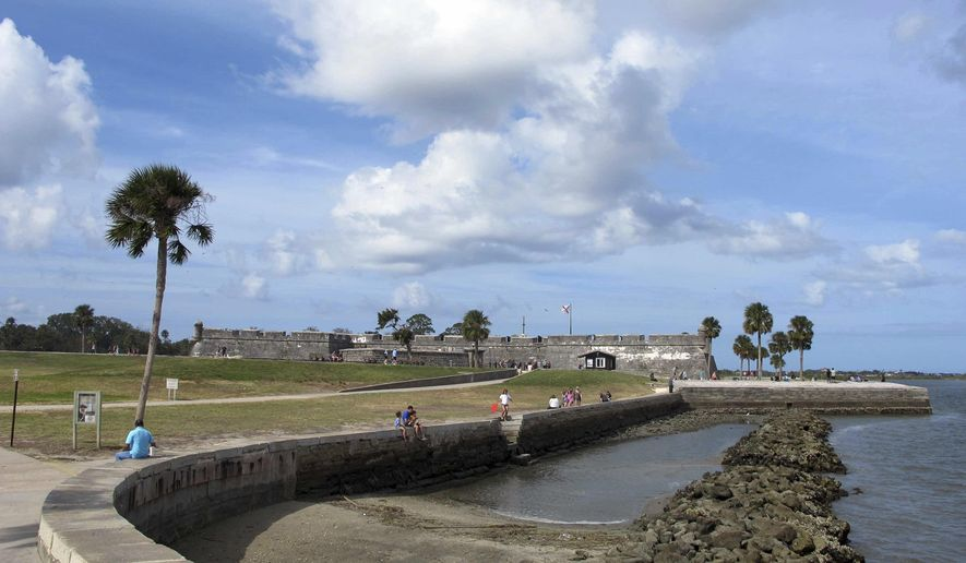 In this Oct. 28, 2016 photo, tourists walk along the waterfront near Castillo de San Marcos in St. Augustine, Fla. More than 1,000 historic buildings in St. Augustine were damaged by Hurricane Matthew's storm surge, even though the Spanish fortress and other well-known structures escaped serious damage. (AP Photo/Jason H. Dearen)
