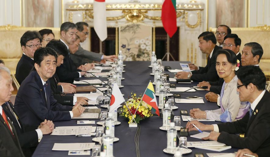 Myanmar Foreign Minister Aung San Suu Kyi, second from right, and Japanese Prime Minister Shinzo Abe, second from left, attend a meeting at Akasaka state guesthouse in Tokyo Wednesday, Nov. 2, 2016. Suu Kyi arrived late Tuesday for a five-day visit amid growing international pressure on her government to get a grip on violence against the persecuted Rohingya Muslim minority following reports of army attacks on the civilian population. (Kimimasa Mayama/Pool Photo via AP)