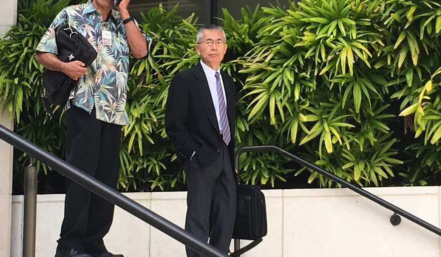 Kauai Community Correctional Center Warden Neal Wagatsuma, left, uses a cellphone while walking out of U.S. District Court in Honolulu on Tuesday, Nov. 1, 2016, with Hawaii Deputy Attorney General Nelson Nabeta. Trial has started in a lawsuit that alleges Wagatsuma subjected female inmates to sexual humiliation and discrimination. (AP Photo/Jennifer Sinco Kelleher)
