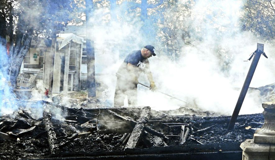 Officials search through rubble of a house fire that claimed the lives of three young children Wednesday, Nov. 2, 2016, in Cash, Ark. One adult was also seriously injured in the fire early Wednesday in Cash, about 100 miles northeast of Little Rock. (Jeff Bricker/The Jonesboro Sun via AP)