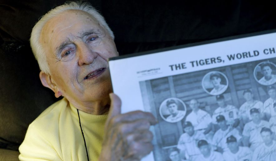 Ed Mierkowicz, the one player still alive who appeared in the 1945 World Series, when the Chicago Cubs reached Game 7 before losing to Detroit points to himself in a group photo at his home, Wednesday, Nov. 2, 2016, in Rochester Hills, Mich. (AP Photo/Carlos Osorio)