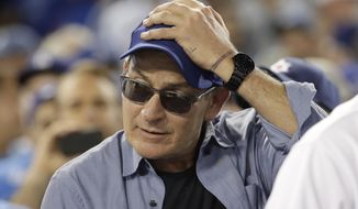 "FILE - In this Oct. 19, 2016, file photo, actor Charlie Sheen reacts during the fifth inning of Game 4 of the National League baseball championship series between the Chicago Cubs and the Los Angeles Dodgers in Los Angeles. Sheen, who played Ricky ""Wild Thing"" Vaughn in ""Major League,"" the iconic film about a sad-sack Cleveland Indians team finally earning postseason success, will be at the climactic World Series Game 7 between the Indians and Chicago Cubs in Cleveland. (AP Photo/David J. Phillip, File)"