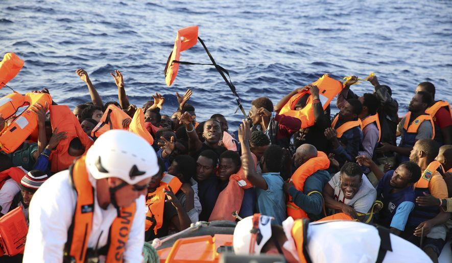 Safety jackets are thrown to migrants on a rubber dinghy rescued by the vessel Responder, run by the Malta-based NGO Migrant Offshore Aid Station (MOAS) and the Italian Red Cross, in the Mediterranean sea, Thursday, Nov. 3, 2016. According to MOAS 147 people, of which 20 women, were rescued.  (Francesco Malavolta/MOAS via AP)