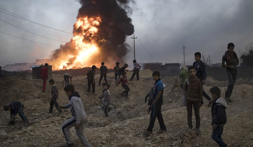 Children play next to a burning oil field in Qayara, south of Mosul, Iraq, Thursday, Nov. 3, 2016. A senior military commander says more than 5,000 civilians have been evacuated from newly-retaken eastern parts of the Islamic State group-held city of Mosul and taken to camps.  (AP Photo/Felipe Dana)