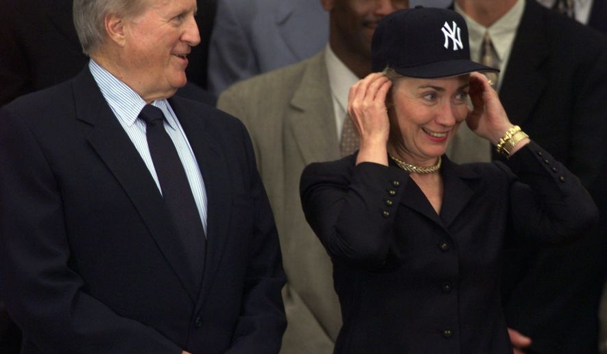 First lady Hillary Rodham Clinton tries on her new New York Yankees hat as she stands next to Yankees owner George Steinbrenner during an event honoring the 1998 World Series champions on the South Lawn of the White House to honor the 1998 World Series Champions, Thursday, June 10, 1999. (AP Photo/Susan Walsh)