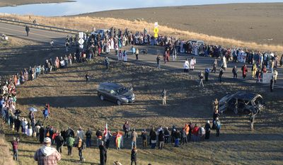 A giant prayer circle is formed to the south of the Backwater Bridge and Highway 1806 as hundreds of clergy of numerous denominations and faiths show support for Dakota Access Pipeline protesters, Thursday, Nov. 3, 2016 in Morton County, N.D. (Mike McCleary/The Bismarck Tribune via AP)