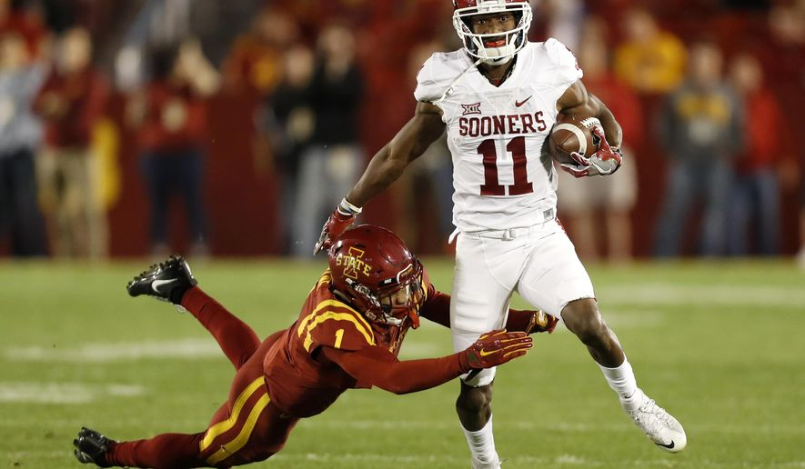 Oklahoma wide receiver Dede Westbrook (11) breaks a tackle by Iowa State defensive back D'Andre Payne, left, during the first half of an NCAA college football game, Thursday, Nov. 3, 2016, in Ames, Iowa. (AP Photo/Charlie Neibergall)