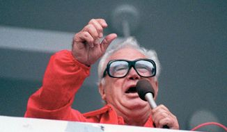 "FILE - In this July 21, 1989 file photo Chicago Cubs' broadcaster Harry Caray sings ""Take Me Out To The Ballgame"" during the seventh inning stretch at Chicago's Wrigley Field.  Brewer Anheuser-Busch honored the legendary sportscaster, who died in 1998 having not seen his beloved Cubbies make it to the World Series, with a video that had him calling the end of Game 7, with the Cubs defeating the Cleveland Indians in an extra-inning 8-7 nail biter. The brewer also resuscitated 1984 Budweiser ad in which the Bud pitch man, and consumer, caught a cold one launched into the Wrigley Field bleachers using a net.(AP Photo/John Swart, File)"