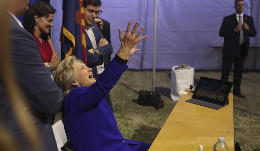 Democratic presidential candidate Hillary Clinton watches the World Series baseball game between the Chicago Cub and the Cleveland Indians after her final campaign rally of the day at Arizona State University in Tempe, Ariz., Wednesday, Nov. 2, 2016. (AP Photo/Andrew Harnik)