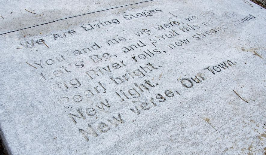 "This Nov. 2, 2016 photo shows the poem ""We are Living Stories,"" by Brenda Hughes, which was stamped into fresh concrete, marking a new arts effort to promote the arts in the community, near the corner of Harrison Street and Lincoln Boulevard, in Muscatine, Iowa.  (Beth Van Zandt/Muscatine Journal via AP)"