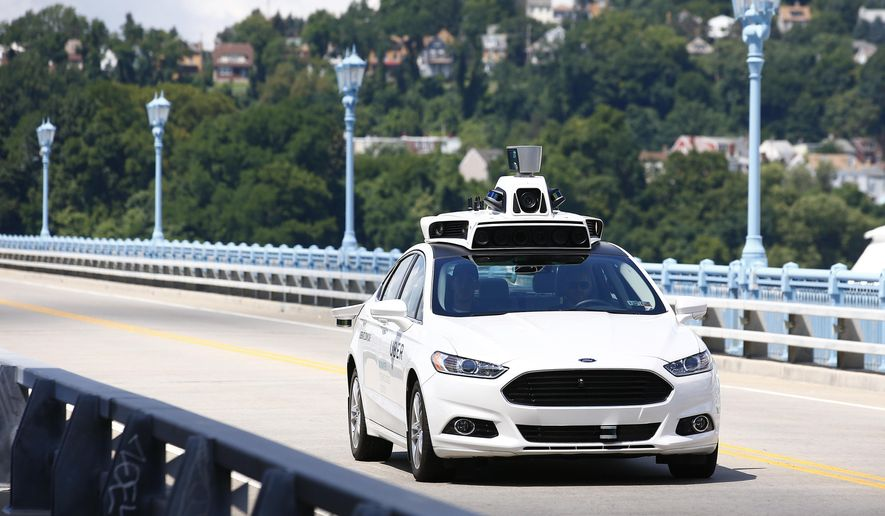 In this Thursday, Aug. 18, 2016, file photo, Uber employees test a self-driving Ford Fusion hybrid car, in Pittsburgh. After taking millions of factory jobs, robots could be coming for a new class of worker: people who drive for a living. (AP Photo/Jared Wickerham, File)