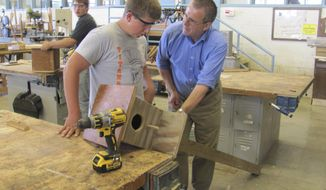 In this Sept. 29, 2016 photo, Industrial arts teacher Jon Welch right, works  with Oakland High School student Jared Smith on a birdhouse project at the school in Oakland, Ill. Welch has helped the Oakland school district rebuild its industrial arts program this fall after the program was on hiatus last year. Students in the industrial arts classes are now working on hands-on projects ranging from building birdhouses to constructing scaled-down modular home sections. (Rob Stroud/Journal Gazette via AP)