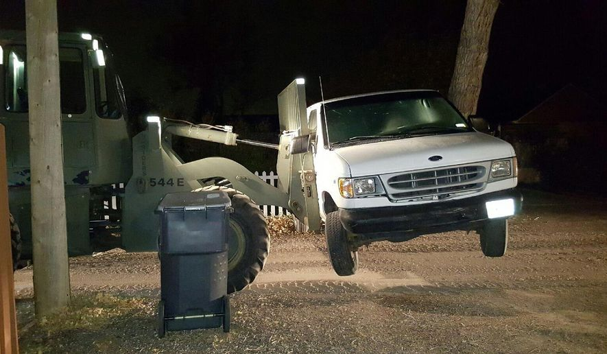 This Sunday, Oct. 30, 2016, photo taken by the Cheyenne Police Department , shows a front-end loader with forklift that was used by a Cheyenne, Wyo., woman to move her van in front of her driveway. Neighbors called police late Saturday night and reported seeing the woman drinking beer while operating the loader. Police charged the woman, Ashley Basich, of Cheyenne, with DUI. Basich has posted $950 bail and awaits a court appearance on Nov. 21. (Cheyenne Police Department)