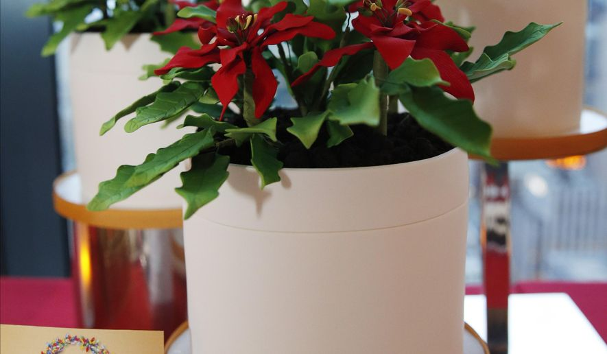 "Oprah's Poinsettia Flower Pot Cake, which looks like a holiday plant, but is actually a chocolate cake with vanilla mousse, is displayed at the headquarters of ""O-The Oprah Magazine,"" Tuesday, Nov. 1, 2016, in New York during a sneak peak of Oprah's Favorite Things, the popular television personality's 2016 Christmas and holiday gift choices. (AP Photo/Kathy Willens)"