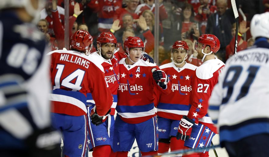 Washington Capitals center Nicklas Backstrom, center, from Sweden, celebrates his goal with teammates in the first period of an NHL hockey game against the Winnipeg Jets, Thursday, Nov. 3, 2016, in Washington. (AP Photo/Alex Brandon)
