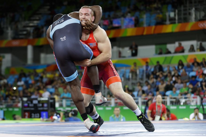 FILE - In this Aug. 21, 2016, file photo, Kyle Snyder, of the United States, in red, competes against Cuba's Javier Cortina Lacerra during the men's 97-kg freestyle wrestling competition at the 2016 Summer Olympics in Rio de Janeiro, Brazil.It's been 32 years since a defending Olympic freestyle medalist returned to compete in the NCAA a year later. There will be two wrestlers to do so this year _ led by Rio gold medalist Kyle Snyder of Ohio State. (AP Photo/Markus Schreiber, File)