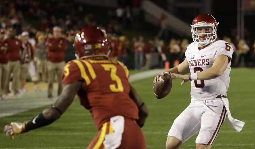 Oklahoma quarterback Baker Mayfield, right, prepares to throw a pass over Iowa State defensive back Mike Johnson, left, during the first half of an NCAA college football game, Thursday, Nov. 3, 2016, in Ames, Iowa. (AP Photo/Charlie Neibergall)