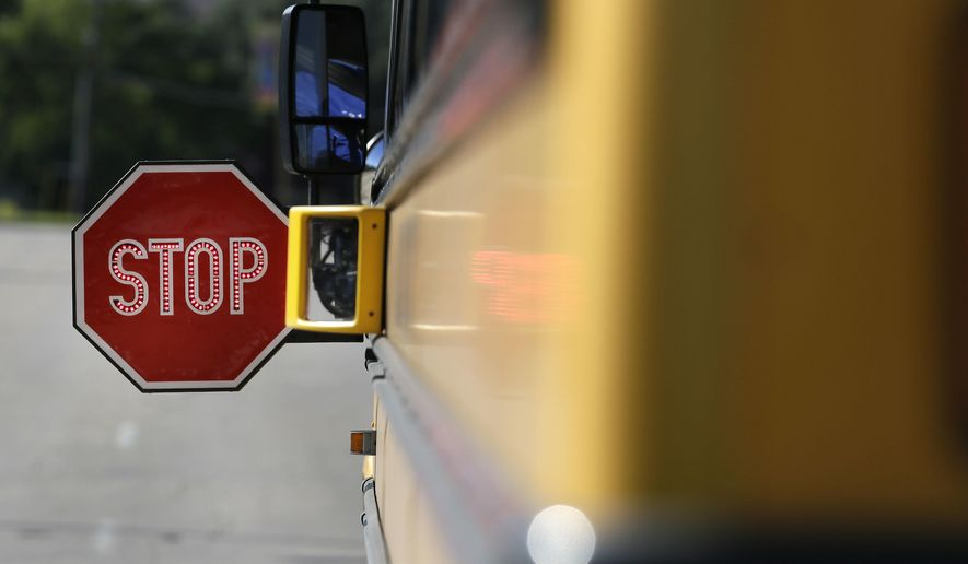In this photo made Thursday, Oct. 27, 2016, a camera sits mounted next to a school bus stop sign in Dallas. A lawsuit contends that two Texas cities are illegally using cameras to ticket drivers alleged to have ignored extended stop signs on school buses, arguing that among other issues, the state Legislature has never authorized local entities to take such action. (AP Photo/LM Otero)