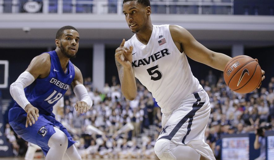 FILE - In this March 5, 2016, file photo, Xavier's Trevon Bluiett (5) drives past Creighton's Maurice Watson Jr. during an NCAA college basketball game in Cincinnati. No. 7 Xavier has its highest preseason ranking as it tries to build upon its breakthrough season and challenge defending national champion Villanova for the Big East title. (AP Photo/John Minchillo, File)