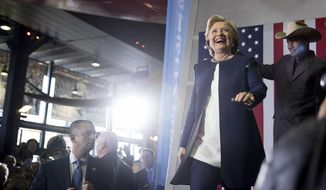 Democratic presidential candidate Hillary Clinton accompanied by retired Pittsburgh Steelers Mel Blount, right, takes the stage at a rally at Heinz Field in Pittsburgh, Friday, Nov. 4, 2016. (AP Photo/Andrew Harnik)