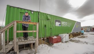 In this Oct. 26, 2016 photo provided by Will Anderson, employee Joe Carr stands outside a new indoor hydroponics farm owned by a local Alaska Native corporation in Kotzebue, Alaska. Arctic Greens is harvesting kale, various lettuces, basil and other greens weekly from the soil-free system and selling them at the supermarket in the community of nearly 3,300. (Will Anderson via AP)